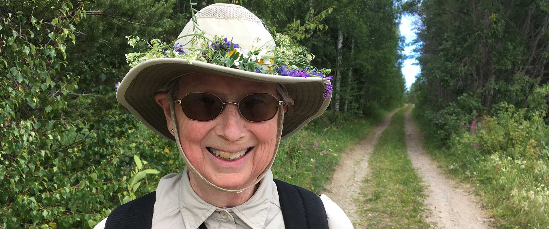 A smiling woman wearing a hat with flowers