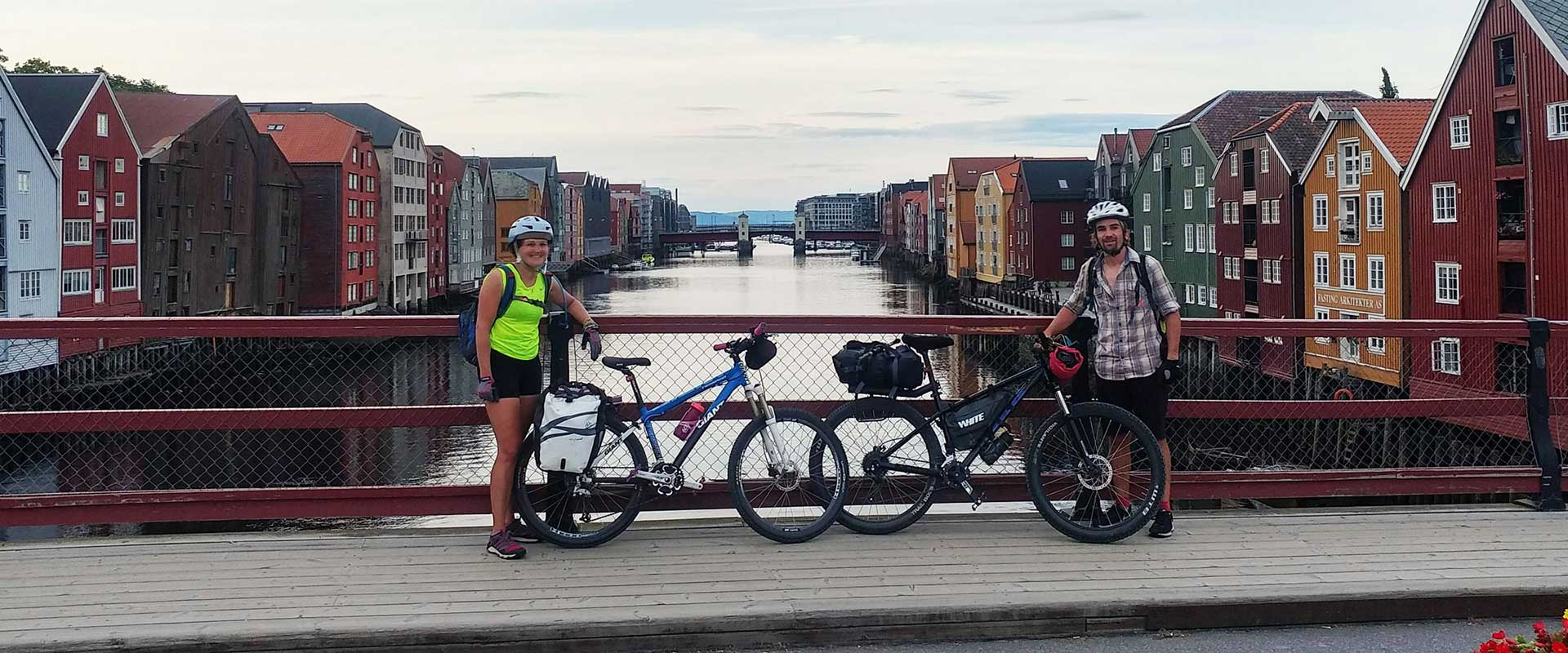 A woman and a man with bikes on a bridge in Trondheim