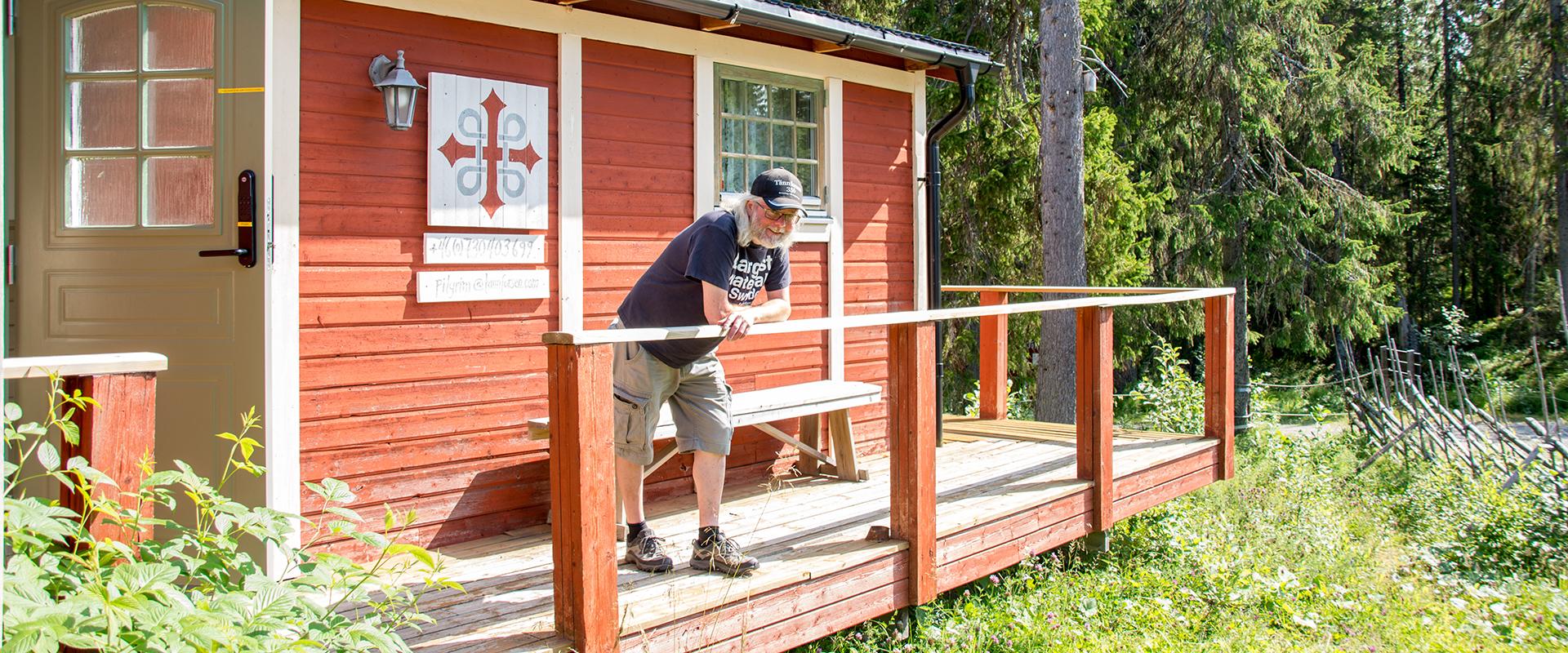 A man standing in front of a red house near Tännforsen.