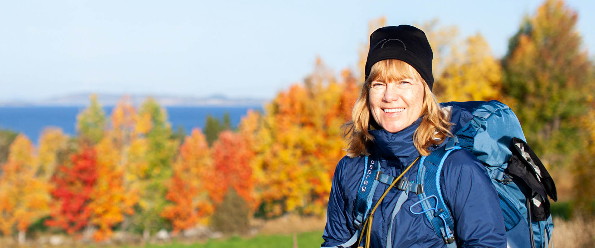 A woman on a hike in front of autumn leaf.